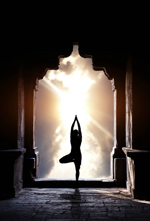 silouette of a woman holding tree pose in an indian temple