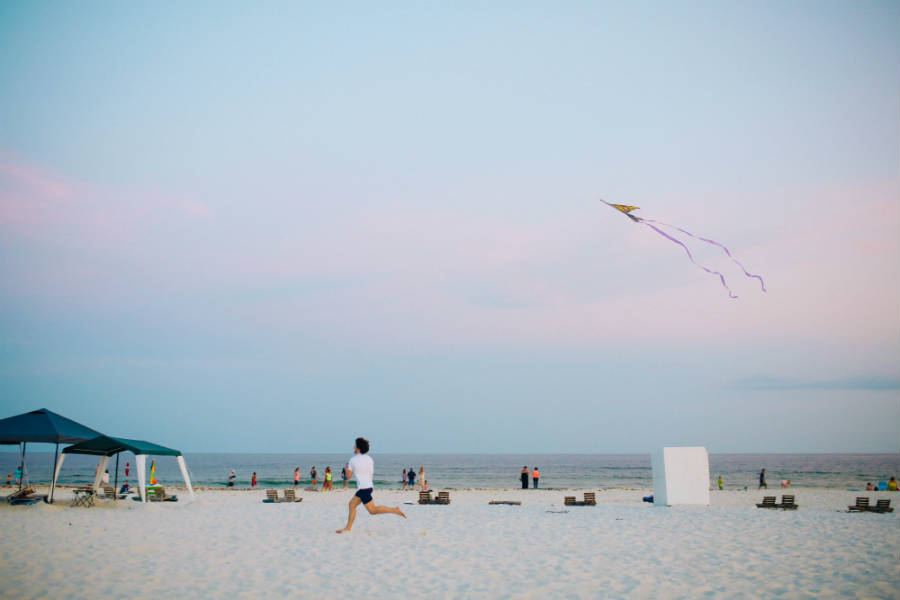 man with kite running on beach